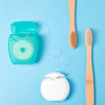 Zahnseidenbehälter und bambuszahnbürsten auf blauem hintergrund