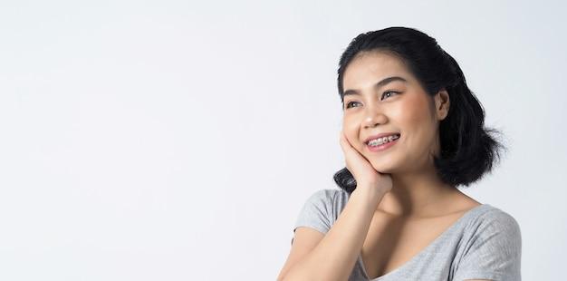 Zahnspangen der jugendlich asiatischen frau, die zahnspangenzähne und kontaktlinsen trägt sie sehr selbstbewusst und stolz präsentieren sich und lächeln auf weißer wand glück teenager lächelnd
