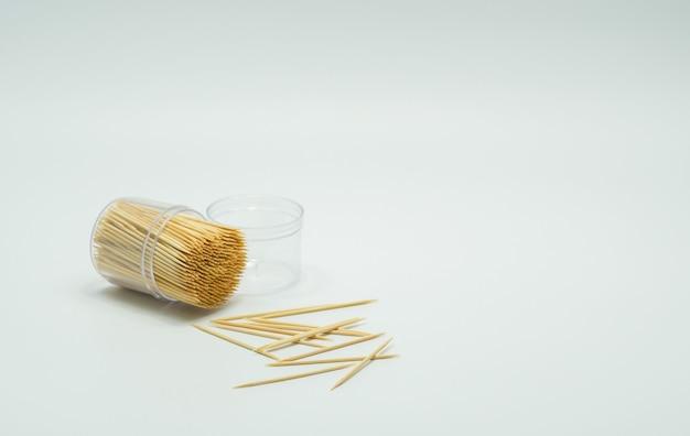 Zahnstocher in einer durchsichtigen plastikflasche. und einige fielen auf den boden, zahnstocherschräge, zahnstocherspritzer