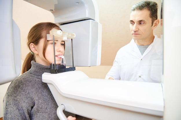 Zahntomographie. mädchen-patient steht in einem tomographen, ein arzt in der nähe des bedienfelds