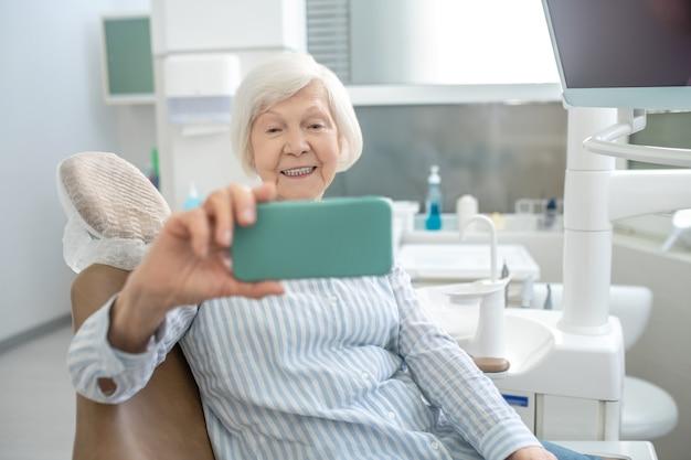 Zahnwiederherstellung. grauhaarige frau macht selfie nach zahnrestauration und sieht zufrieden aus