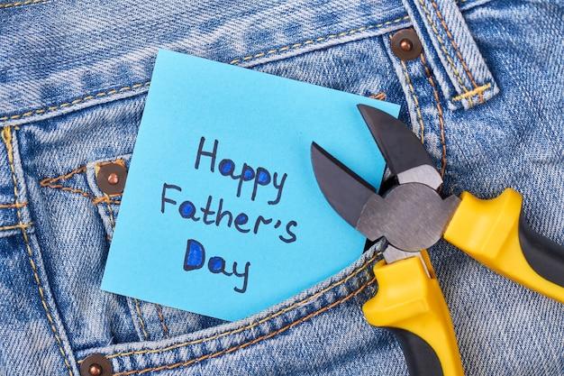 Zange in der nähe der vatertagskarte. jeanstasche mit zange. männliches geschenk für den besten papa.