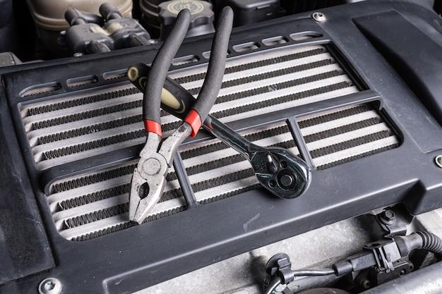 Zange und ratsche liegen unter der motorhaube eines ölkühlers. konzept der autoreparatur und werkzeuge im autoservice