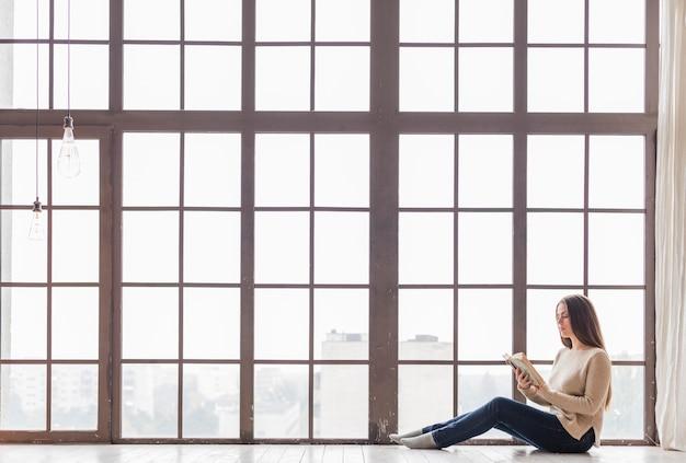 Zangenfrau, die auf fußboden nahe dem fensterlesebuch sitzt