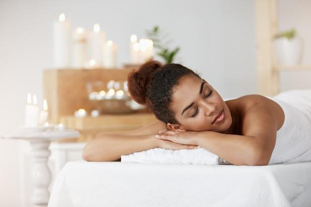 Zarte afrikanische frau, die entspannend mit geschlossenen augen im spa-salon ruht.