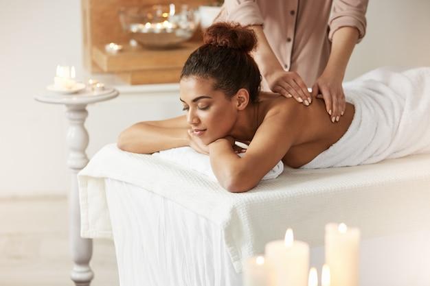 Zarte afrikanische frau lächelnd, die massage mit geschlossenen augen im kurort genießt.