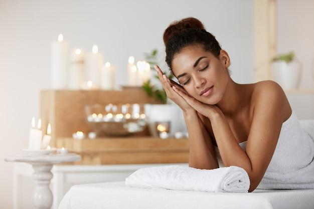 Zarte afrikanische frau lächelnd, die sich mit geschlossenen augen im spa-salon ruhend ausruht.