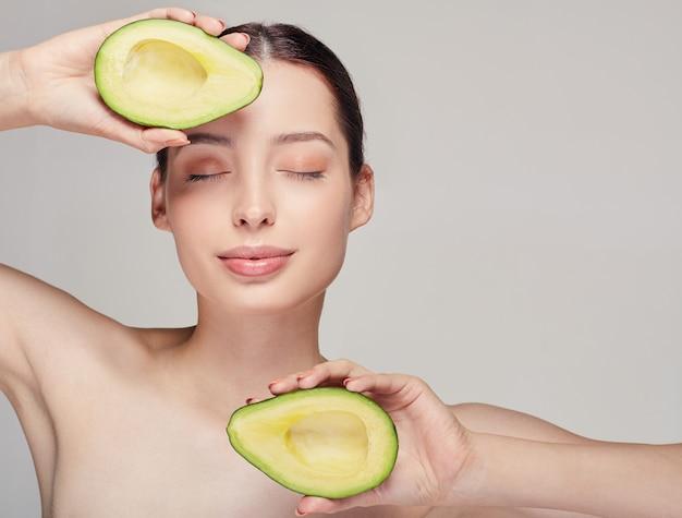 Zarte braunhaarige dame mit mit avocado oben und unten in händen