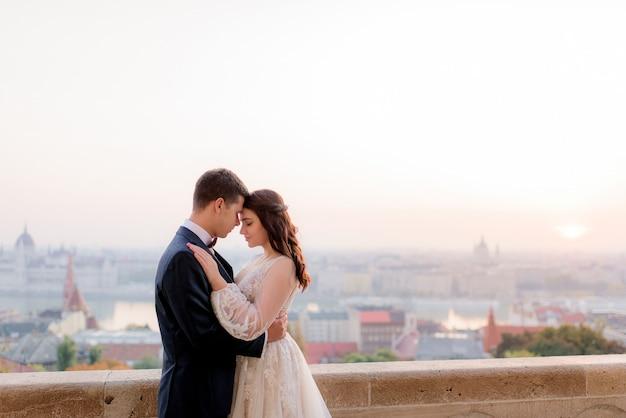 Zarte braut und bräutigam umarmen sich mit schönem blick auf eine große stadt am warmen sommerabend