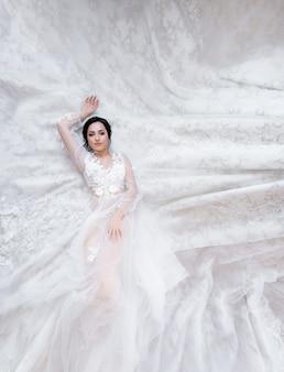 Zarte brünette kaukasische braut liegt auf dem stoff eines luxushochzeitskleides