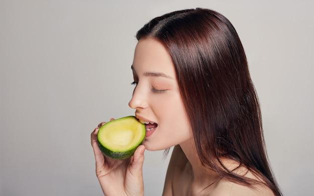 Zarte dame mit perfekter reiner glanzhaut, die avocado isst
