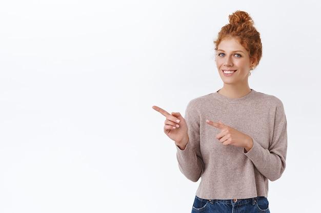 Zarte, elegante rothaarige frau mit lockigem haar im brötchen, kuscheligen pullover tragen, mit den fingern nach links zeigen, fragen zum produkt stellen, in die kamera lächeln, etwas über weiße wand bewerben