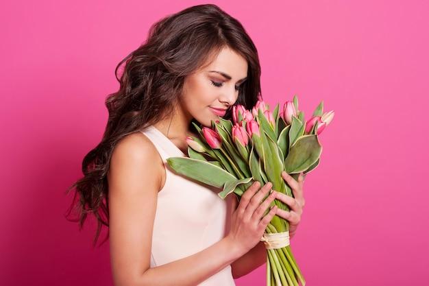 Zarte frau der schönheit, die frühlingsblumen riecht