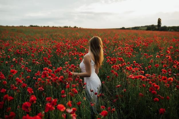 Zarte frau im weißen kleid, das im mohnfeld steht und schöne landschaft genießt