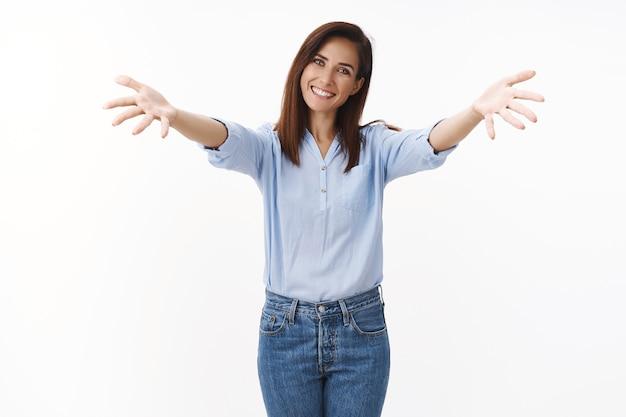 Zarte freundliche hausfrau breitet sich angenehm seitlich die hände aus, lächelt freudig, lädt freunde ein, grinst wartende umarmung, romantische umarmungen, weiße wand fröhlich stehen, gäste begrüßen
