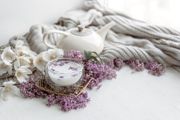 Zarte frühlingskomposition mit frischen blumen, einem glas milch und einem strickelement