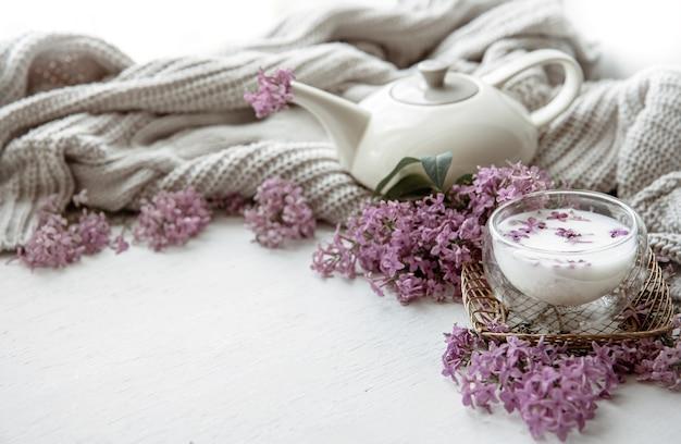 Zarte frühlingskomposition mit lila blüten, einem glas milch und einem strickelement.