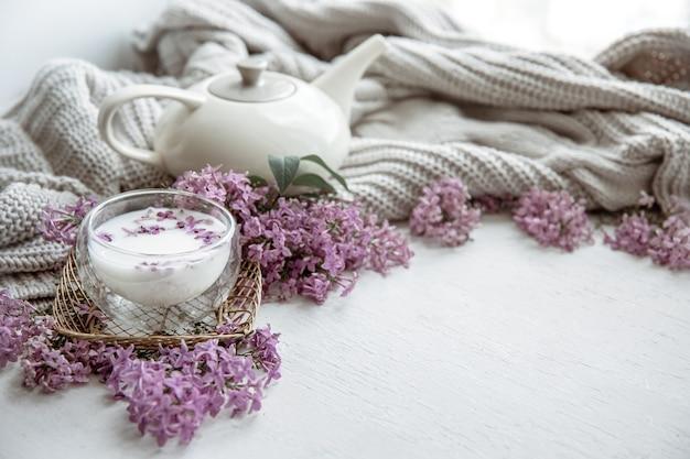 Zarte frühlingskomposition mit lila blüten, einem glas milch und einem strickelement