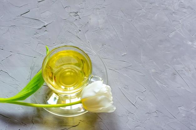Zarte frühlingstulpen und eine tasse grüner tee auf grauem zement