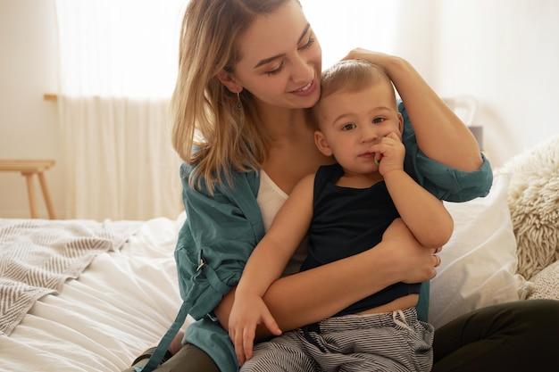Zarte glückliche junge blonde mutter sitzt im schlafzimmer mit charmantem kleinkindsohn auf ihrem schoß, schaut ihn mit liebe und zuneigung an und streichelt sanft die haare. mutter, die mit babybaby zu hause verbindet