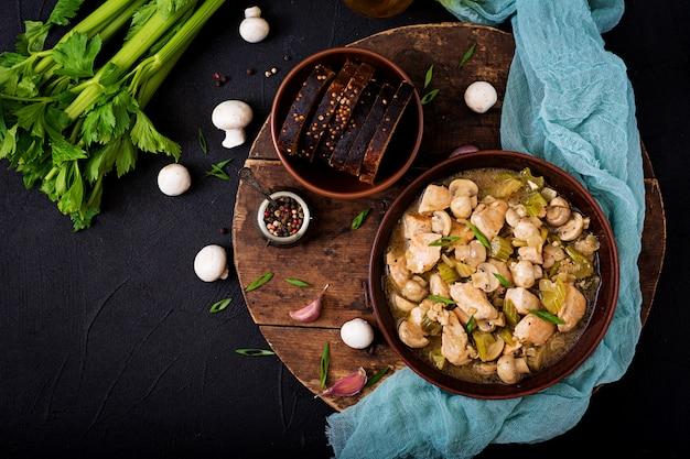 Zarte hähnchenfiletstücke mit champignons und sellerie in leichtem bier gedünstet. flach liegen. ansicht von oben