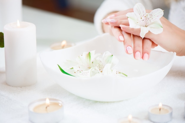 Zarte hände der schönheit mit maniküre, die blumenlilie hält.