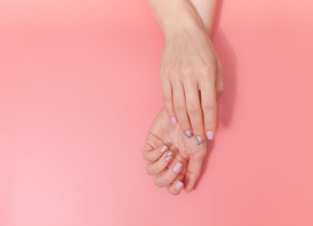 Zarte hände mit perfekter nackter maniküre auf modischem pastellrosahintergrund. platz für text