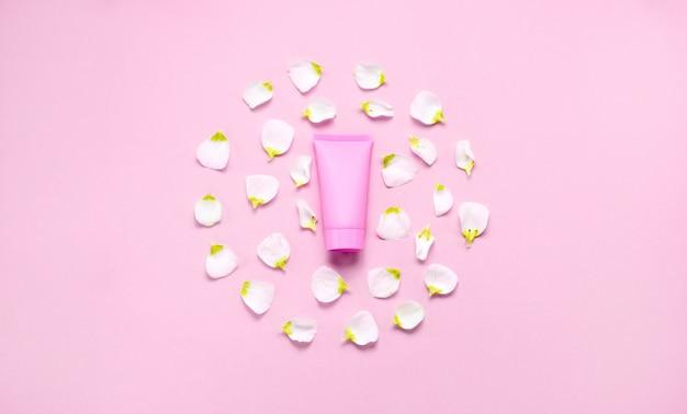 Zarte hautpflege kosmetische weibliche flatlay. draufsicht kreative zusammensetzung von gesichtscreme, flaschen und gläsern mit kosmetik- und blumenblättern auf abstraktem hintergrund