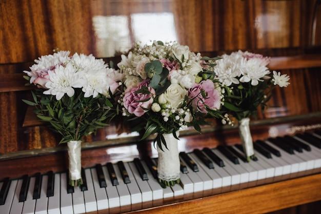 Zarte hochzeitssträuße für braut und brautjungfern auf dem altmodischen klavier