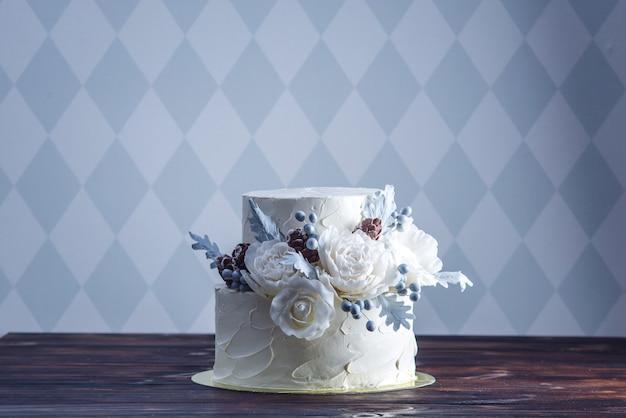 Zarte hochzeitstorte mit weißer koje, dekoriert mit einem originellen design unter verwendung von mastixrosen