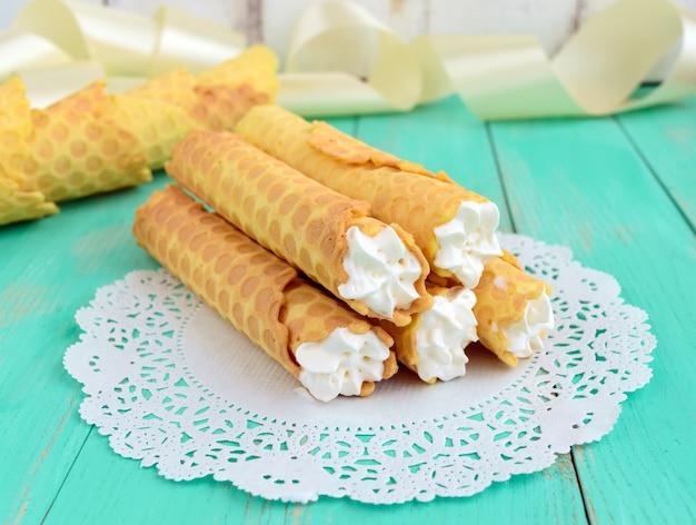 Zarte honigwaffeln in form von röhrchen, gefüllt mit luftcreme auf weißer spitzenserviette. nahansicht.