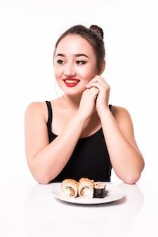 Zarte junge frau sitzt am weißen tisch und hat einen teller mit sushi
