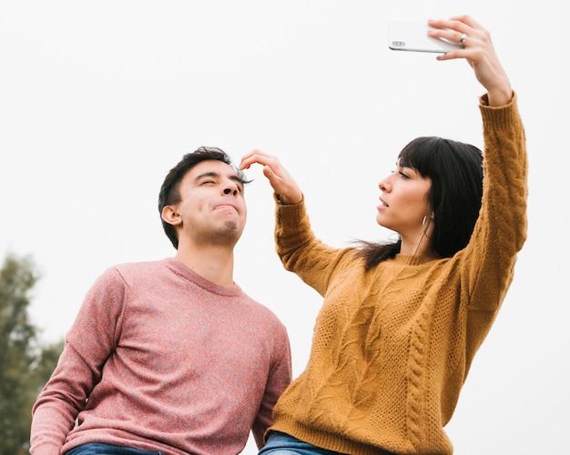 Zarte junge paare, die zum selfie fertig werden