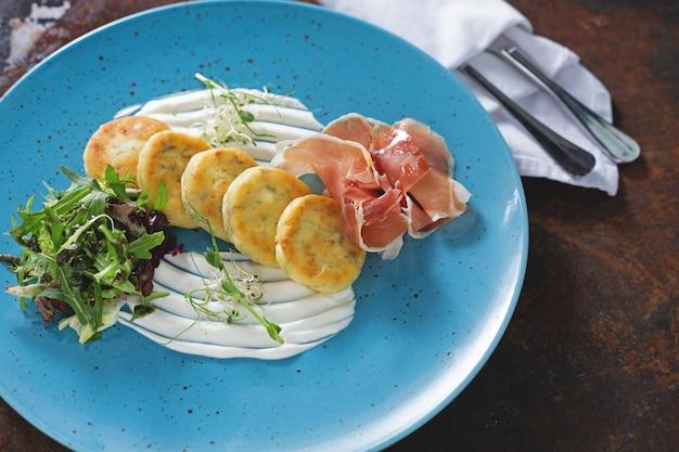 Zarte käsekuchen mit parma und rucola auf blauem teller