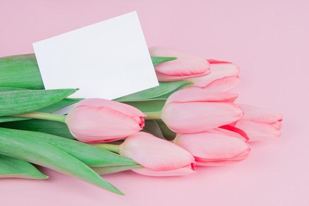 Zarte karte blüht tulpen mit einer notiz auf einem rosa hintergrund