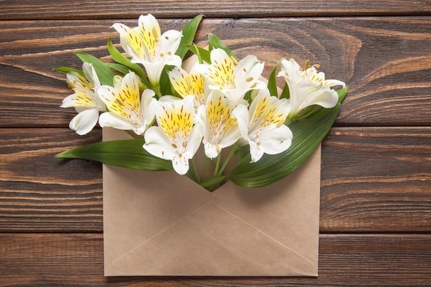 Zarte kleine orchideen der weißen blumen in einem listigen postumschlag auf einem hölzernen hintergrund