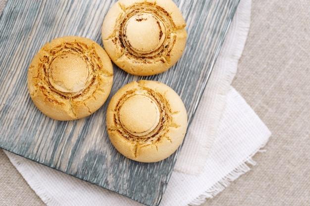Zarte knusprige kekse in form von pilzen. gebackene süße kekse auf hölzernem brett mit copyspace. ansicht von oben.