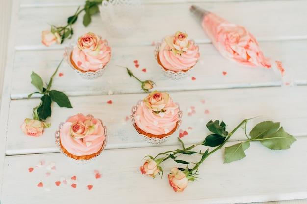 Zarte leckere muffins mit einer rosa creme, verziert mit echtem ros