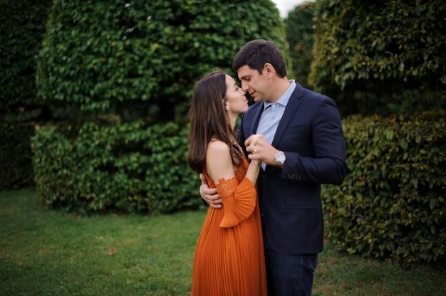 Zarte liebesgeschichte der schönen frau im orangefarbenen kleid und des mannes im eleganten anzug