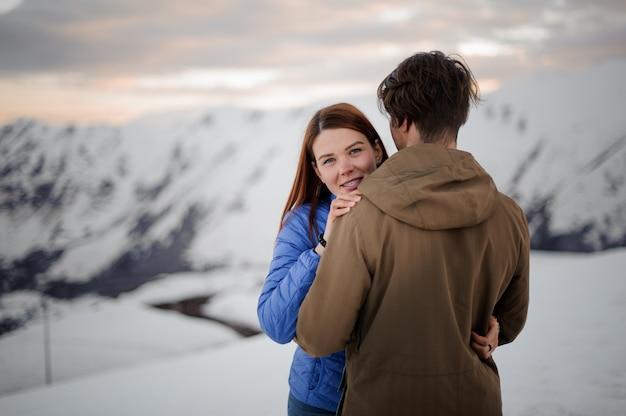 Zarte liebespaare umarmen sich vor der kulisse der schneeberge