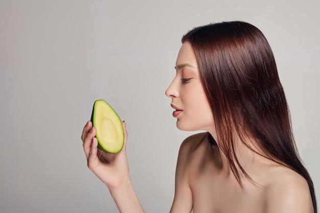Zarte nackte dame, die avocado betrachtet