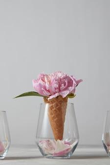 Zarte rosa pfingstrose in einem wafer-kegel in einem glas mit blütenblättern, die auf einem grauen steintisch stehen, kopierraum. ansicht von oben. konzept der glückwünsche zum muttertag