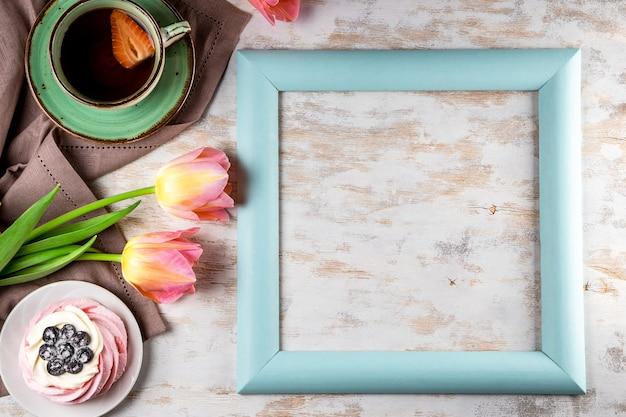 Zarte rosa tulpen, eine tasse tee und pavlova-kuchen auf weißem holz