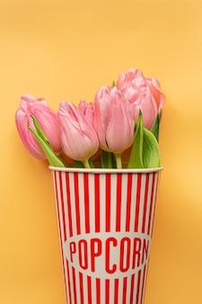 Zarte rosa tulpen innerhalb der rot gestreiften popcornschale auf pastellgelbem hintergrund. flach liegen. speicherplatz kopieren. platz für text. konzept des internationalen frauentags, des muttertags, des osters. valentinstag lieben tag