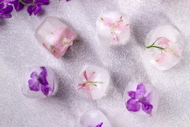 Zarte rosa und lila blüten eingefroren in eiswürfeln auf hellgrauem hintergrund. ansicht von oben