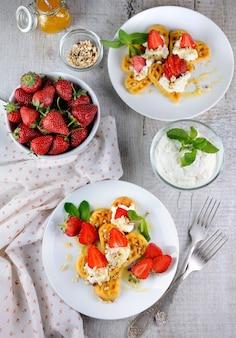 Zarte, schmelzende köstliche belgische waffeln mit schlagsahne, erdbeeren, gewürzt mit erdnüssen und honig.