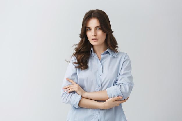 Zarte schöne junge frau mit dunklem welligem haar im blauen hemd, das ernstes aussehen hat und für foto im artikel über junge familien aufwirft.
