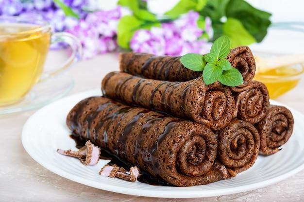 Zarte schokoladenpfannkuchen auf einem haufen und eine tasse kräutertee mit honig