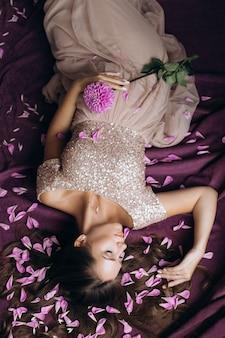 Zarte schwangere frau im rosafarbenen kleid, das auf dem violetten plaid liegt, das mit rosafarbenen blumenblättern bedeckt wird