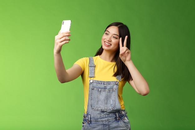 Zarte süße asiatische brünette frau hält smartphone posiert selfie-look telefon-bildschirm fotografieren ...